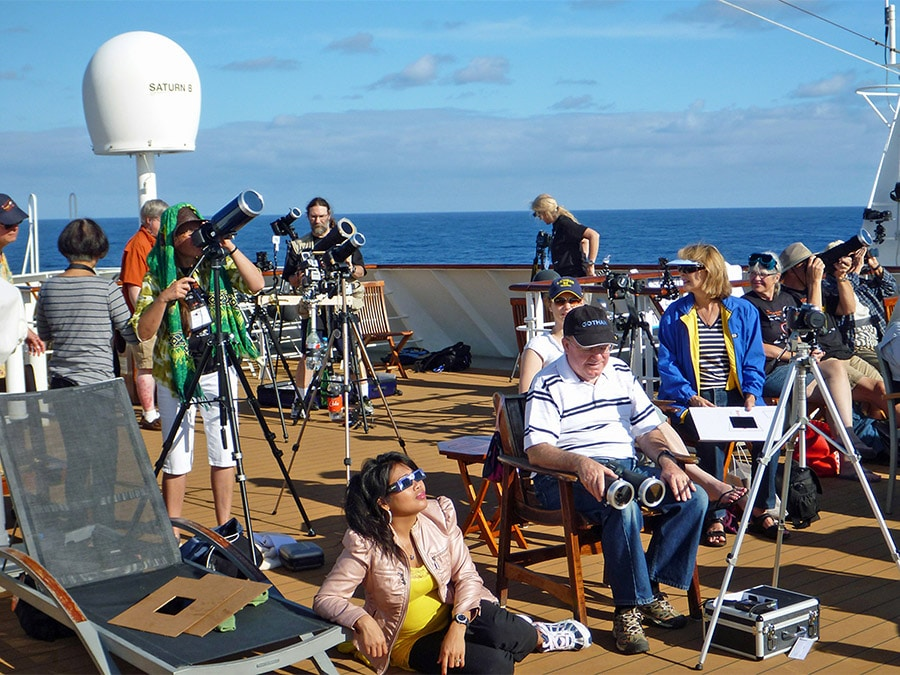 Eclipse seekers wait for totality on the deck of a boat.